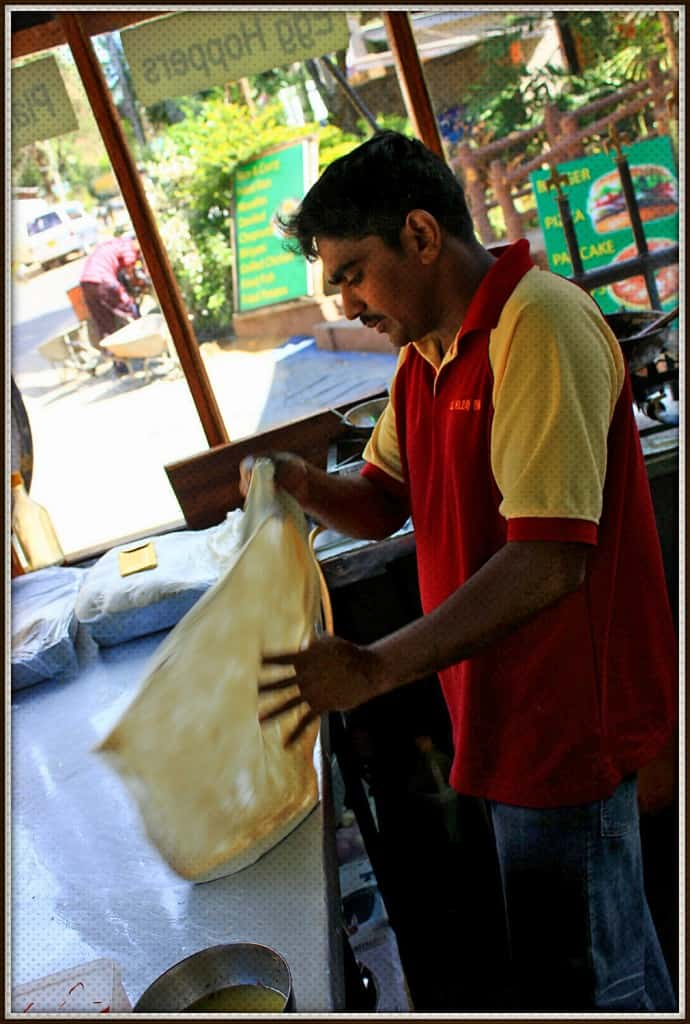 Street food in Sri Lanka | The chief is spinning roti dough around in his hands until it gets very thin.