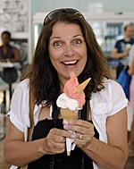 Suzanne Courtney, from the travel blog, The Travelbunny, holding a huge ice cream cone with a equally huge grin on her face