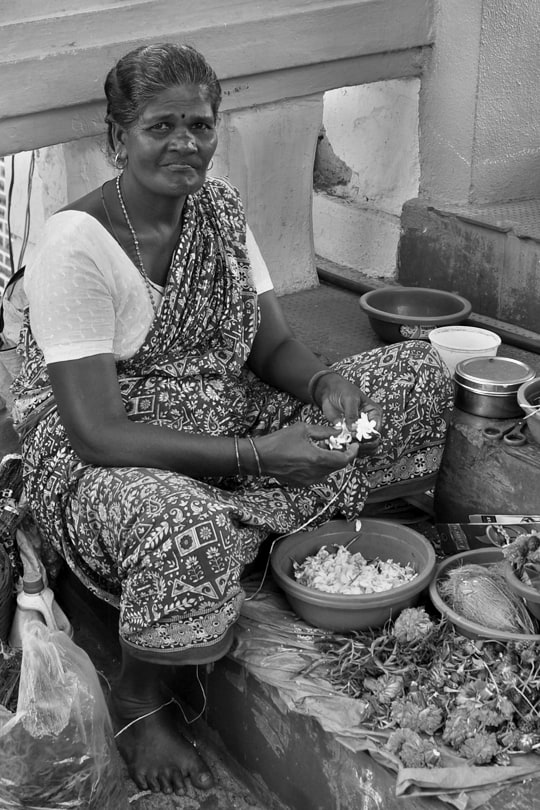 Selling offerings outside a Hindu temple from a collection of portraits from Goa, India