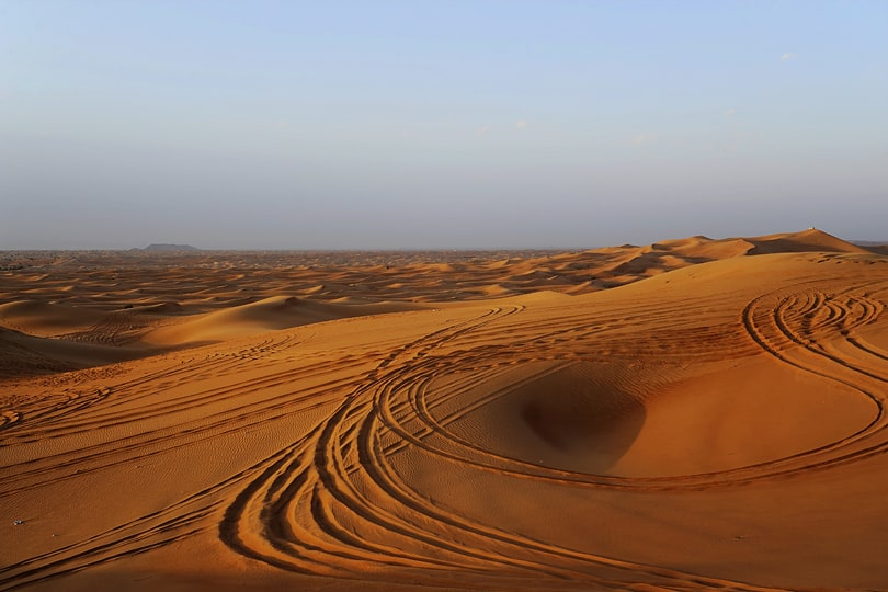 A never ending expanse of sand dunes lit by a golden light as the sun sinks low in the sky | Things to do in Abu Dhabi