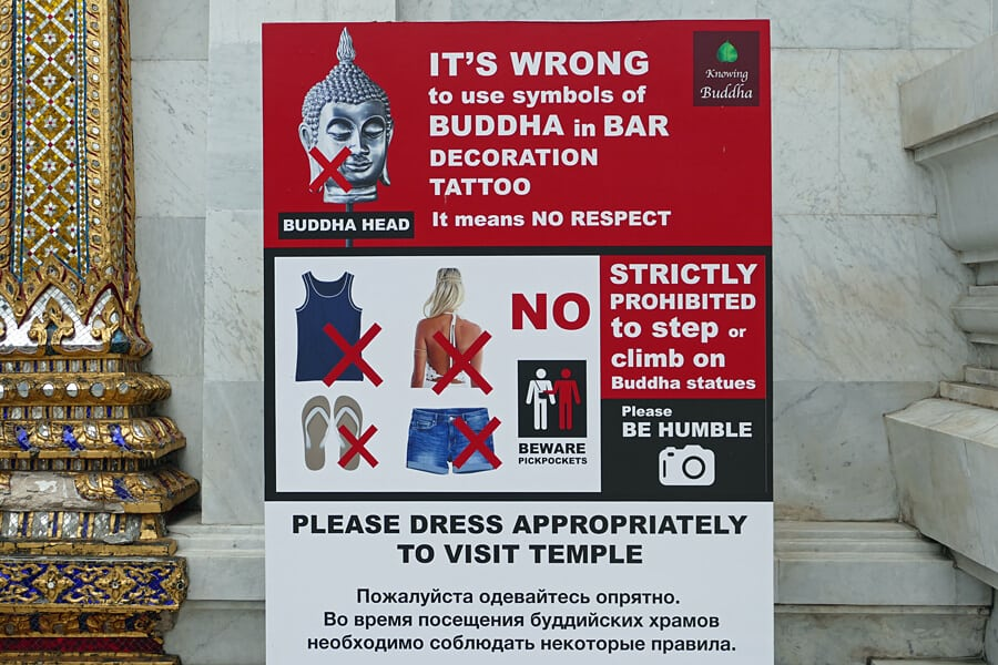 A sign by a temple in Bangkok requests visitors dress appropriately and cover tattoos to help avoid any cultural offence