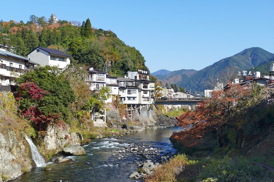 The town of Gujo-Hachiman - a river runs through the town, bubbling over large rocks. The banks are covered in evergreen trees and red Japanese maples