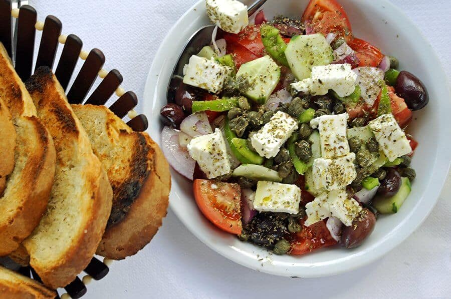 Santorini salad with sweet local tomatoes, cucumber, feta cheese, olive and capers