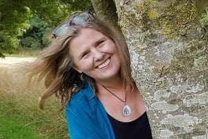 Head and should shot of Kathryn Burrington, author of 'Travel With Kat' smiling as she peeps round from behind a tree