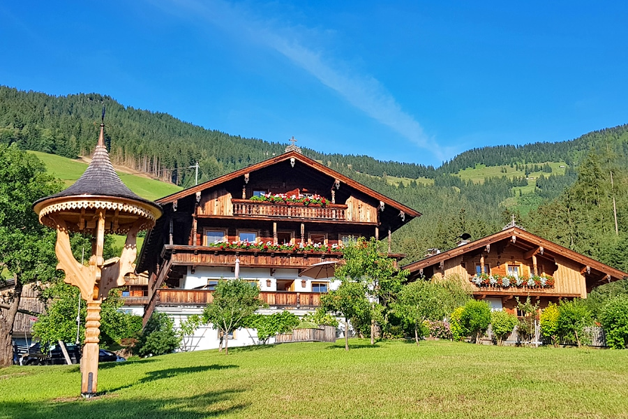 Two picturesque wooden chalets with red geraniums lining their balconies in Alpbach, the prettiest village in Austria