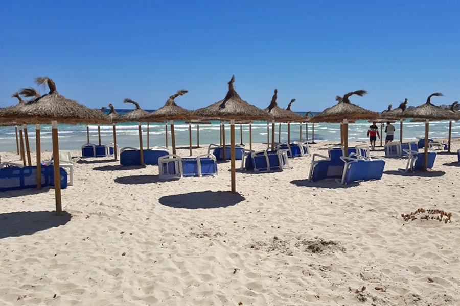 The white sands, thatched parasols and blue sunbeds of a nearby beach in Sa Coma, Mallorca