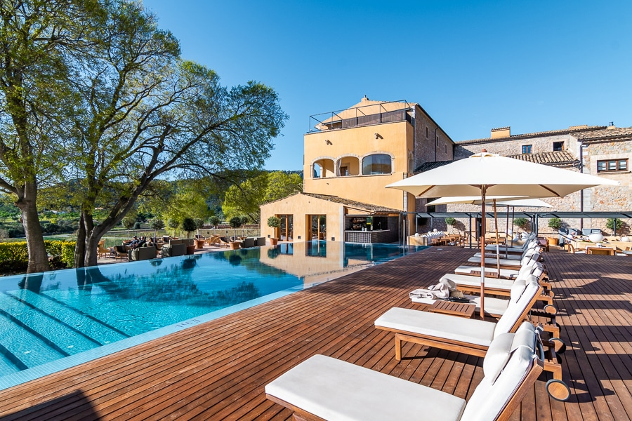 The lovely swimming pool, wooden decking and smart white sunbeds by the Son Brull Hotel & Spa, one of the best hotels in Mallorca