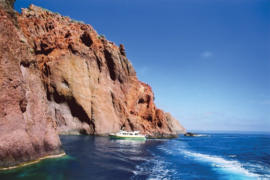 Tourist boat dwarfed by the red granite cliffs, Scandola Nature Reserve