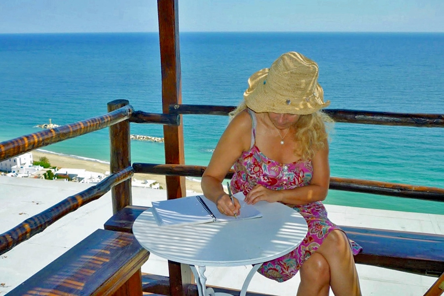 Solo Holidays | A women sits writing on a shady terrace by a snady beach lapped by a beautiful deep blue sea