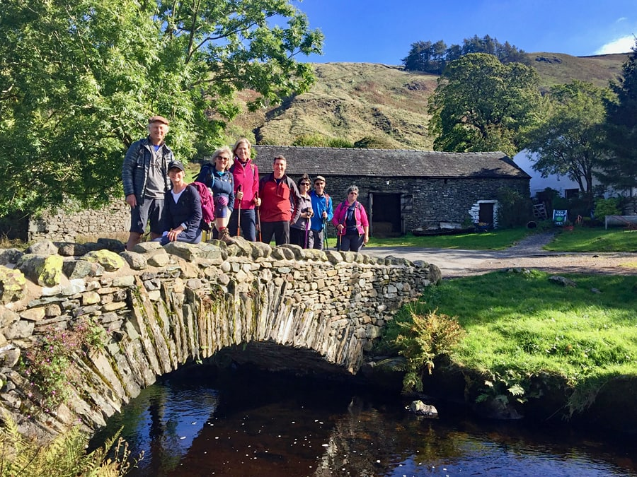 Agroup of walkers standing on an old stone bridge across a stream