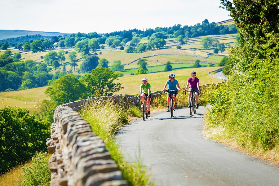 Three cyclists riding along a lane edge with an old stone wall, through the rolling green hills of the Yorkshire countryside