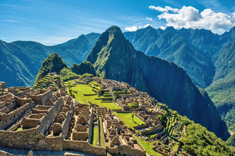 The majestic Machu Picchu, Peru, the ruins of the city in the foreground with towering mountains behind it, under a clear blue sky with a few fluffy white clouds