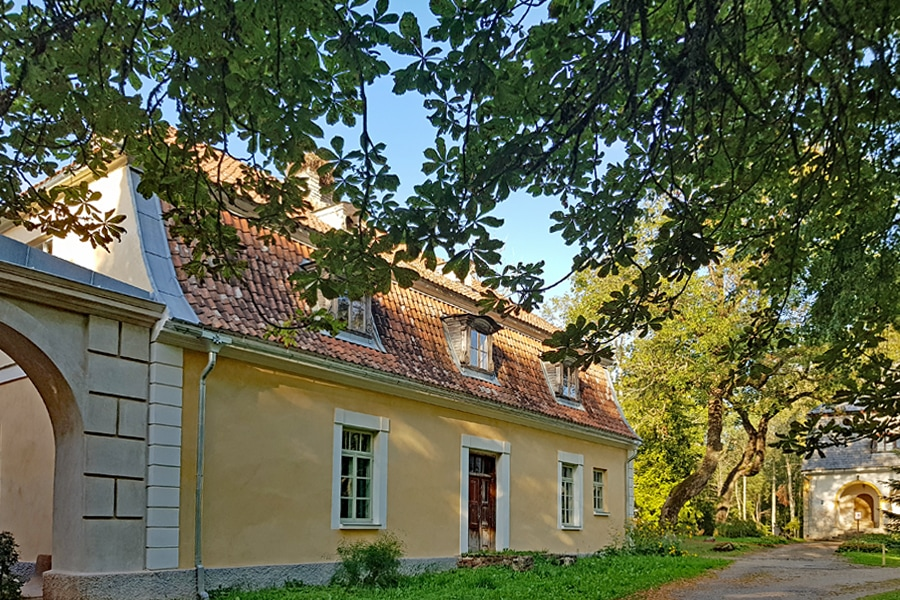 A restored section of Kabile Manor in western Latvia with pale yellow facade and terracota tiled roof