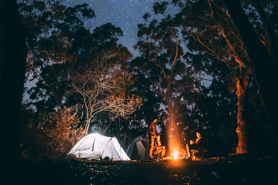 Tents and a roaring fire in a forest clearing under a starry night sky