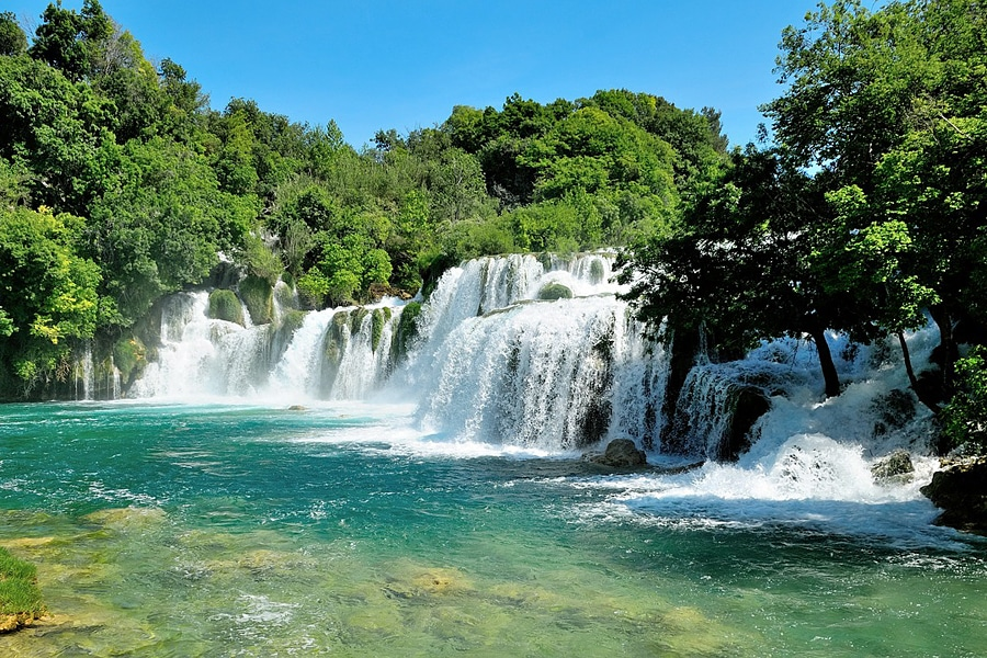 Tumbling waterfalls flowing into clear tourquise water, Krka, Croatia