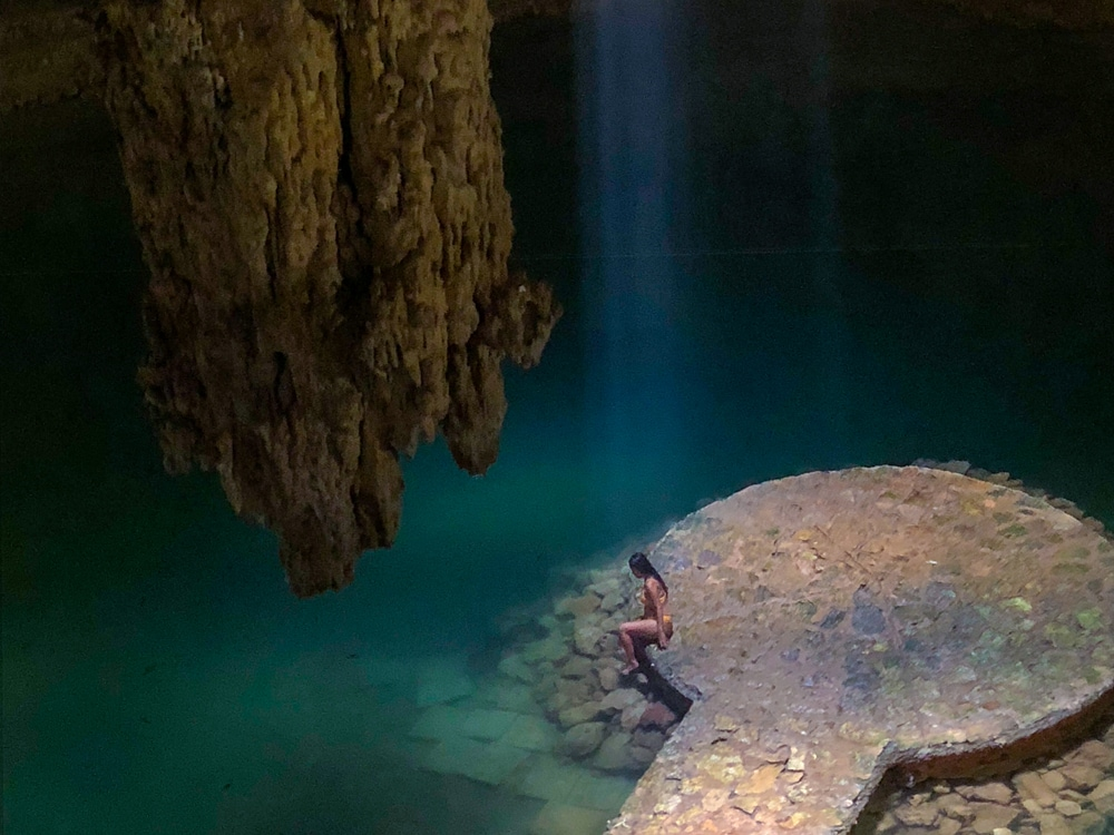 A single beam of light falls on a girl sitting on a platfom in cave cenote in Mexico - Cenote Suytun - one of th emost unique places to swim in the world