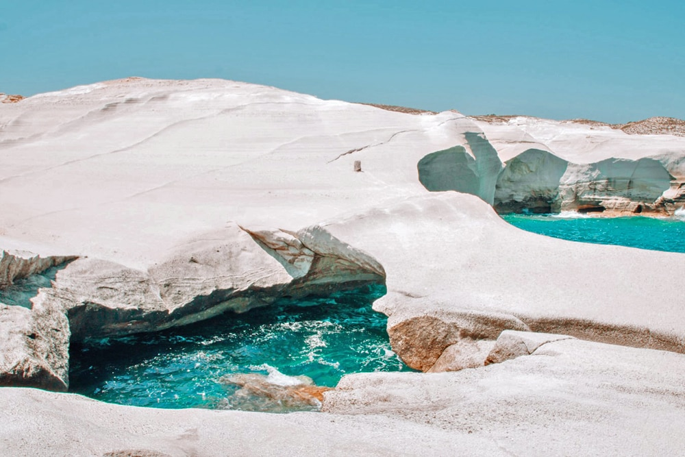 Sarakiniko Beach - The lunar like landscape of white rock sculpted by the waves forms a stark contrawst against the electric blue water